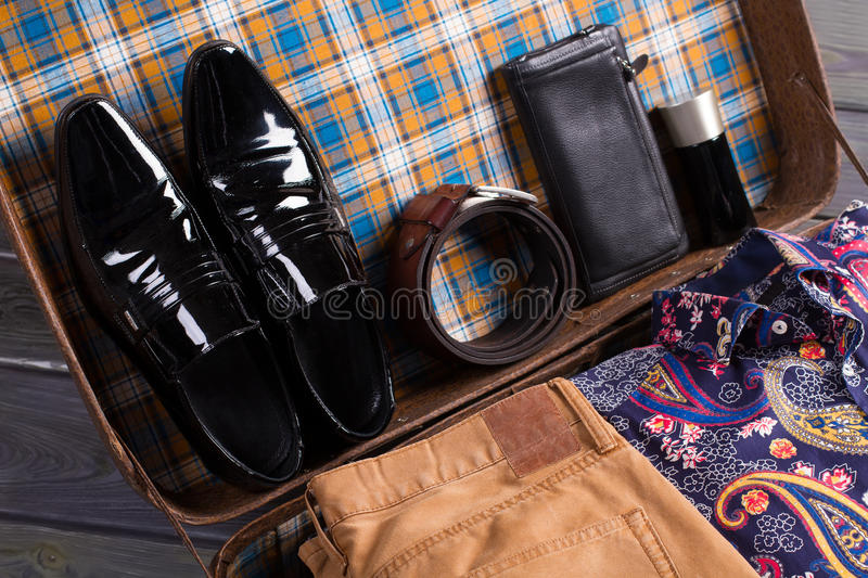 Still life of menswear. Men's shoes, accessories and clothes in old suitcase. Still life of menswear stock photos