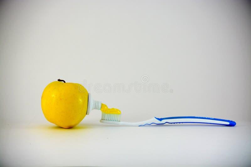 Still life metaphor. White background. Yellow apple royalty free stock photo