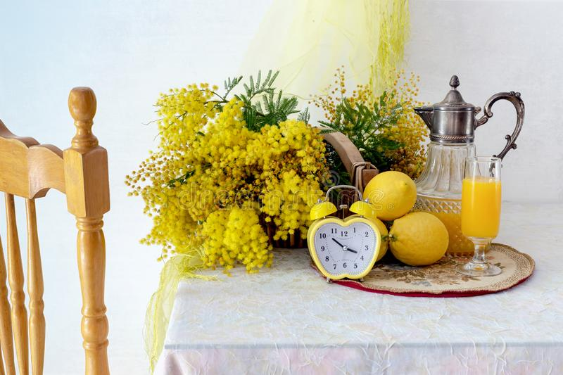Still life with mimosa branches, lemons and juice. royalty free stock photography