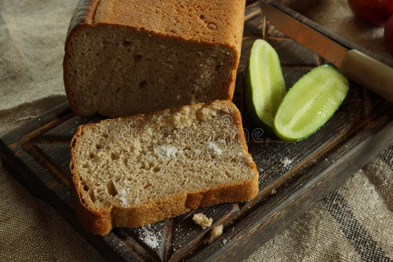 Still life with mouth-watering fresh bread and salt, next to a fresh cucumber from a vegetable garden , rustic style stock images