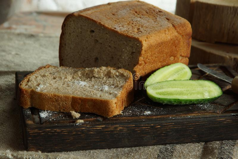 Still life with mouth-watering fresh bread and salt, next to a fresh cucumber from a vegetable garden in a village, rustic style stock images