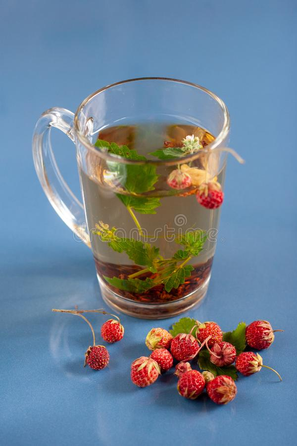 Still life of a mug of herbal tea on blue ceramic tiles with dust texture and reflection. Near scattered strawberries. Focus on th stock image