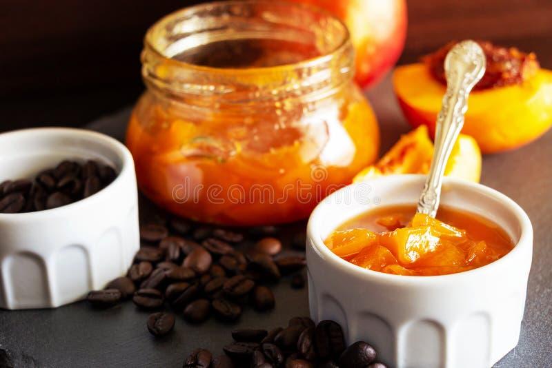 Still life with Nectarine jam in ramekin. Dark background. Selective focus. Close up. Still life with Nectarine jam in ramekin. Dark background. Selective focus stock images