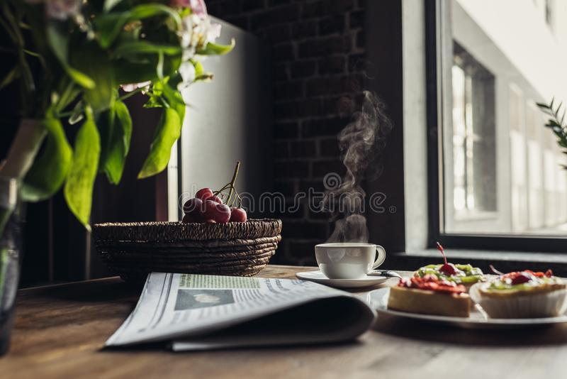 Still life of newspaper, breakfast with cakes and hot coffee on kitchen table in front stock image