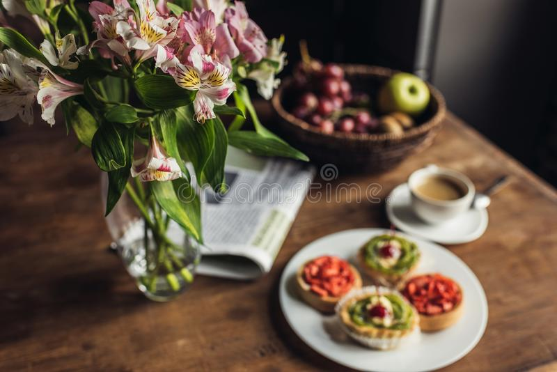 Still life of newspaper, flowers and breakfast with cakes and hot coffee on kitchen table in front royalty free stock photo