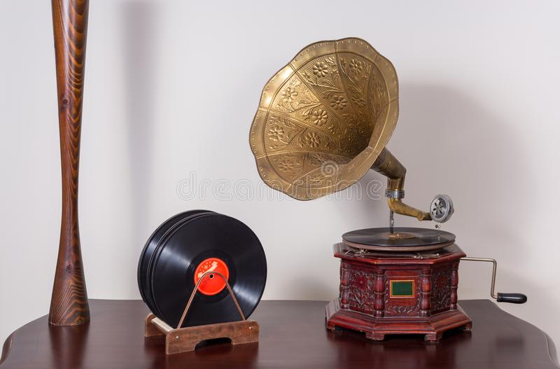 Still life of a nineteenth century phonograph and vinyl records. Still life of a nineteenth century phonograph gramophone and vinyl records on a wooden table and royalty free stock photography