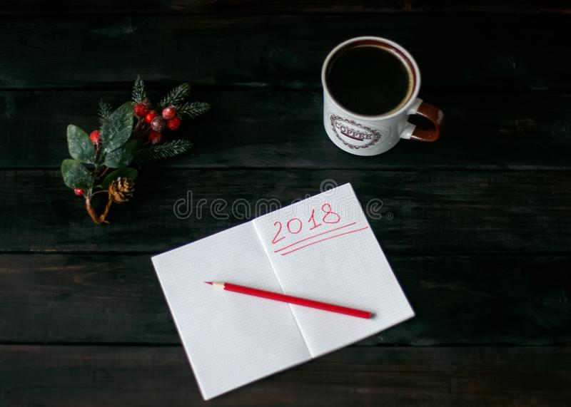 Still-life with a notebook with a red inscription 2018, a Cup of coffee stock image