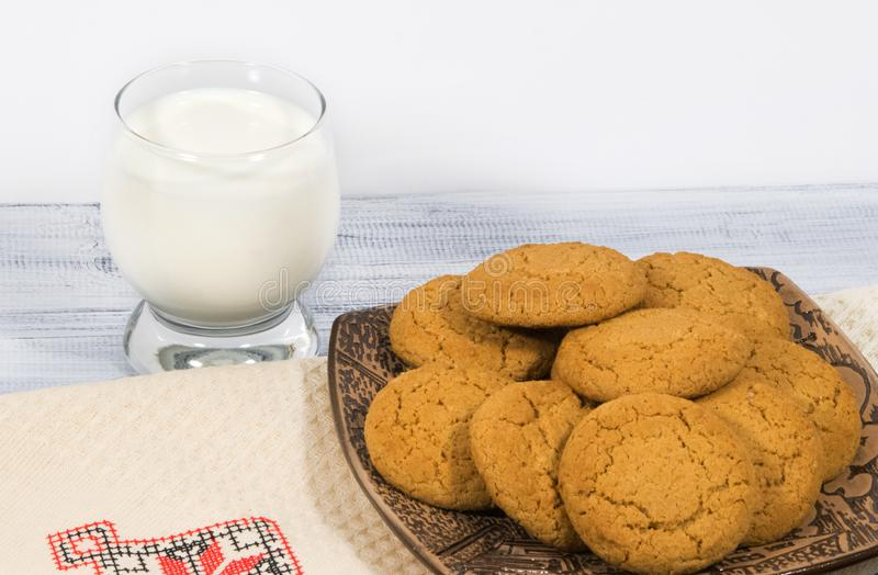 Still-life with oatmeal cookies and a glass of milk. Oatmeal cookies in a ceramic plate on a wooden background and a glass of milk. Embroidered cotton napkin stock photography