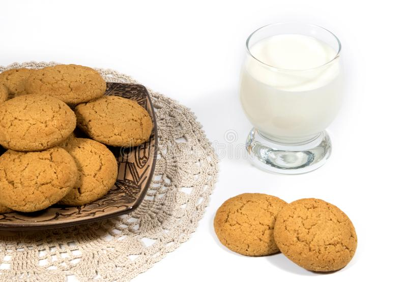 Still-life with oatmeal cookies and a glass of milk. Oatmeal cookies in a ceramic plate on a wooden background and a glass of milk. Knitted cotton napkin stock photography