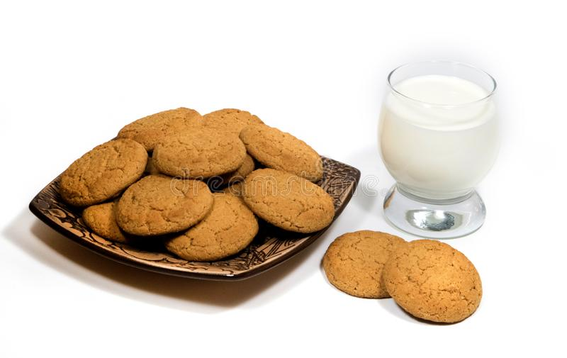 Still-life with oatmeal cookies and a glass of milk. Oatmeal cookies in a ceramic plate on a white background and a glass of milk. Confectionery still life stock image