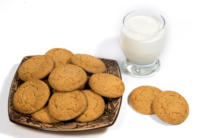 Still-life with oatmeal cookies and a glass of milk. Oatmeal cookies in a ceramic plate on a white background and a glass of milk. Confectionery still life stock photography