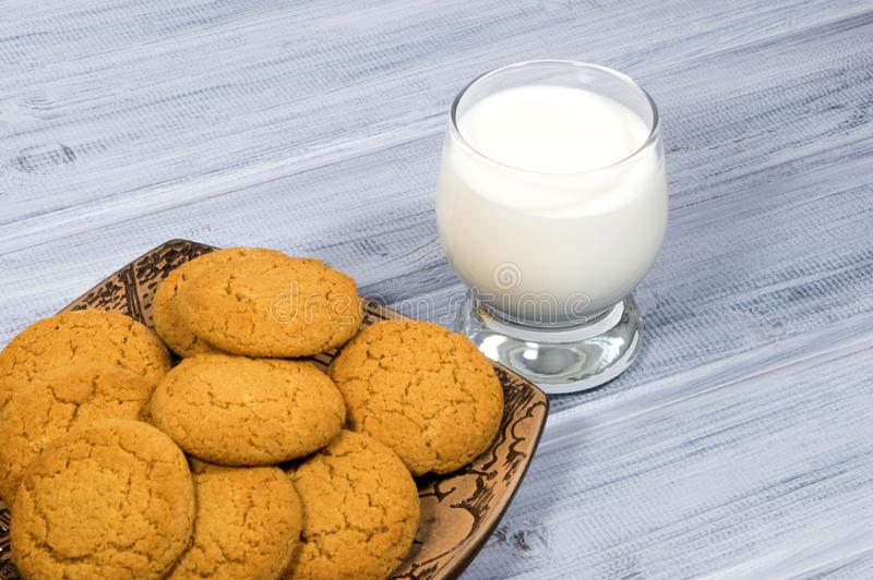 Still-life with oatmeal cookies and a glass of milk. Oatmeal cookies in a ceramic plate on a wooden background and a glass of milk. Embroidered cotton napkin stock image