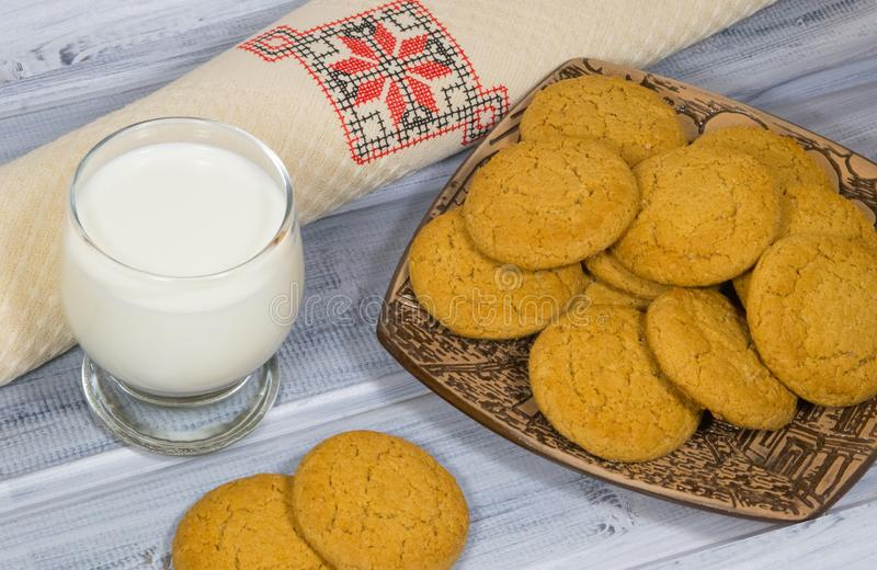 Still-life with oatmeal cookies and a glass of milk. Oatmeal oven in a ceramic plate on a wooden background and a glass of milk. Embroidered cotton napkin stock photography