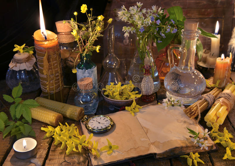 Still life with old book, candles, glass bottles and healing herbs royalty free stock image