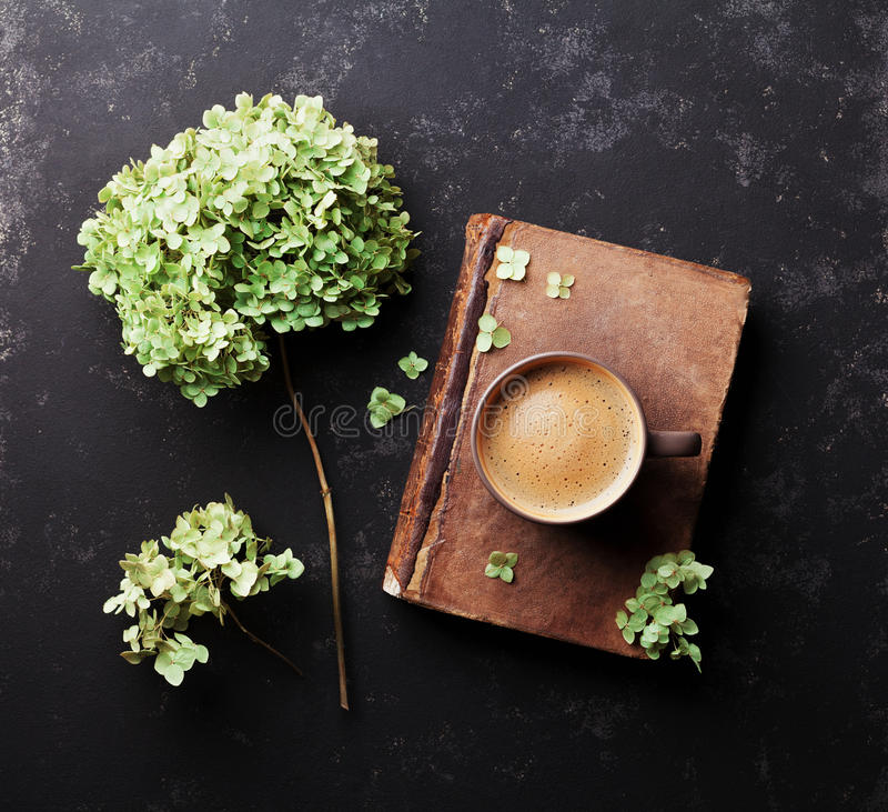 Still life with old book, coffee and dried flowers hydrangea on black vintage table top view. Flat lay styling. royalty free stock photography