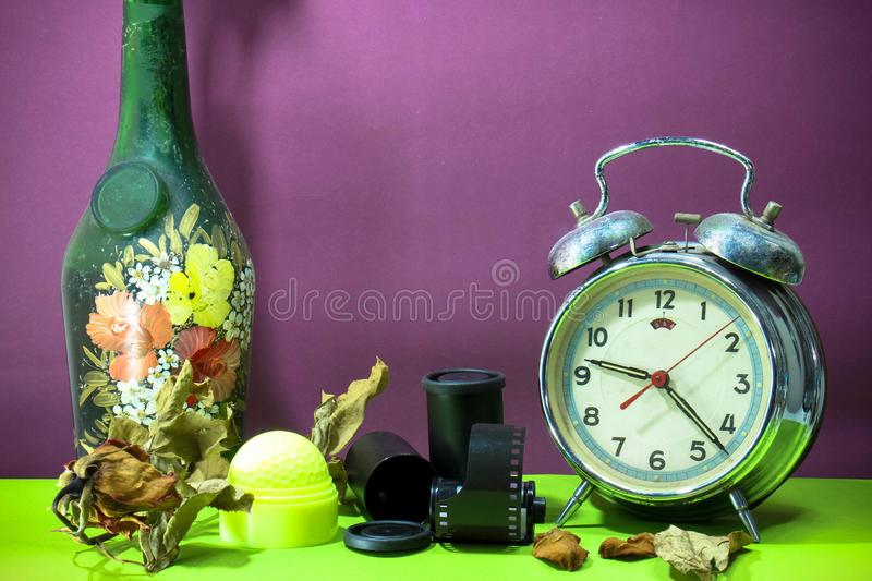 Still life with old broken alarm clock, old glass vase, dead rose, negative film, green golf, colorful background stock photos
