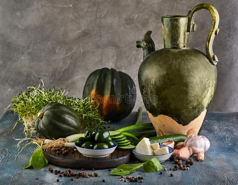 Still life with an old jug, Kabocha Squash, sprouts with olives and cheese on a gray background and a wooden stand stock image