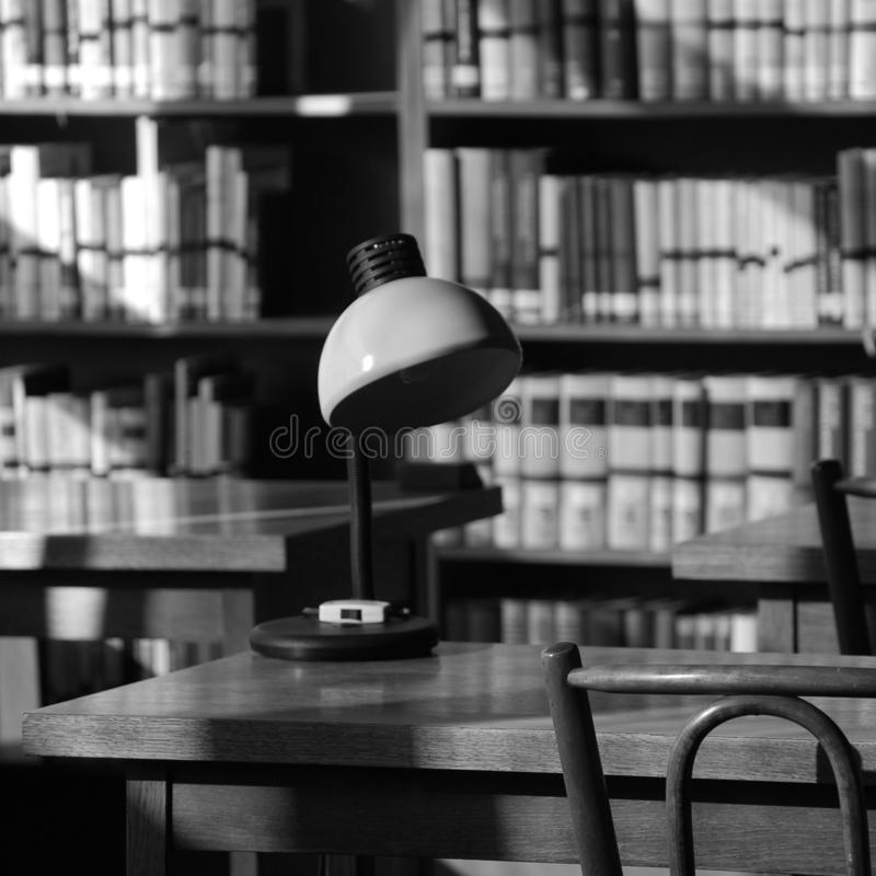 Still life in an old library with a lamp on a table stock images