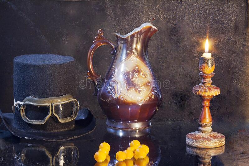 Still-life. Old things from past centuries. Burning candle. Old hat. Jug. royalty free stock images