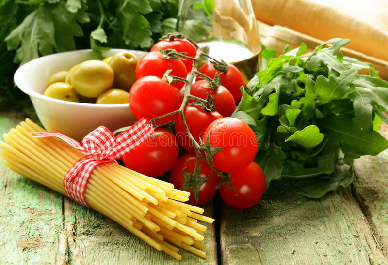 Still life of olives, herbs, tomatoes and Italian pasta royalty free stock image