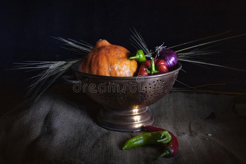 Still life. Orange pumpkin, red and green chilli peppers, purple onions, and dried wheat rings in a metal cup. Still life on a black background. Orange pumpkin royalty free stock photos