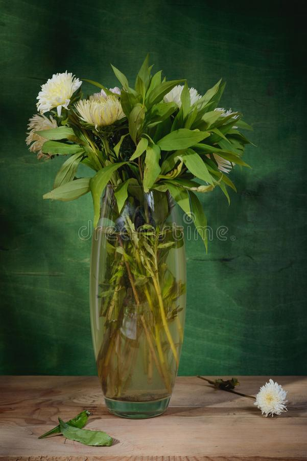 Still-life painting. Beautiful flowers in a vase. Wooden background royalty free stock photos