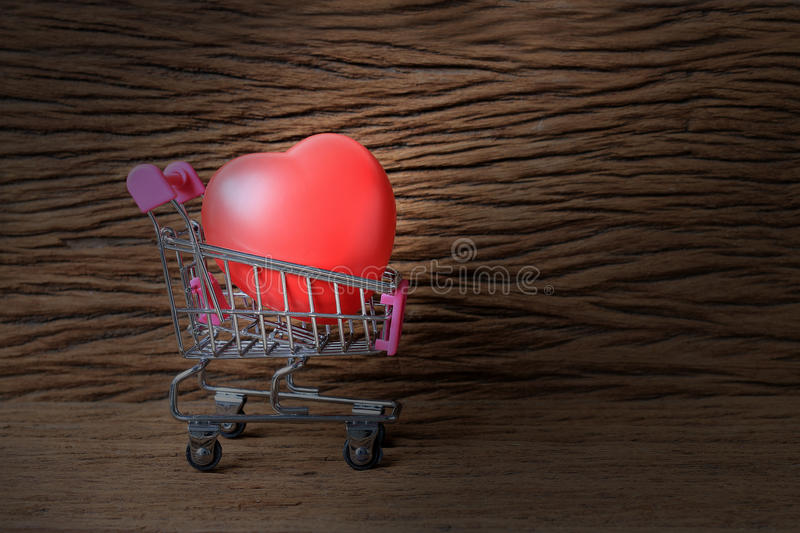 Still life painting photography with red heart shape over old beautiful wooden background. Image for love shopping concept.  royalty free stock images