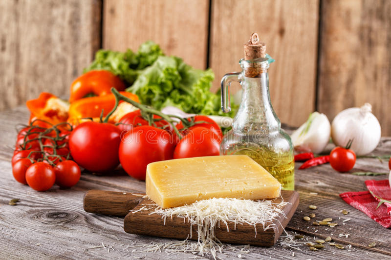 Still life with Parmesan cheese and fresh vegetables. In the Italian rustic style. royalty free stock photography
