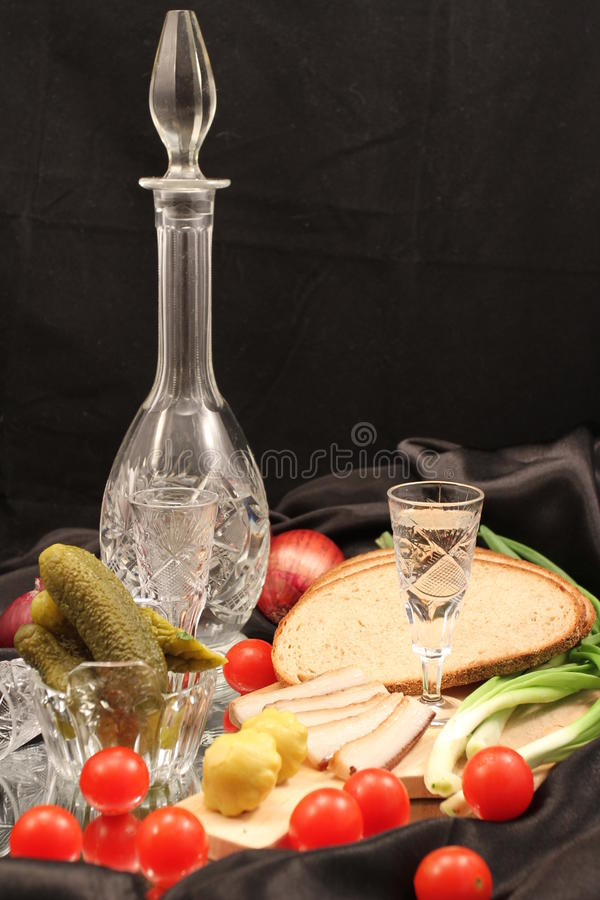Still life: party in the Russian style. Vodka in the countess with snack on a black backgroundn royalty free stock images