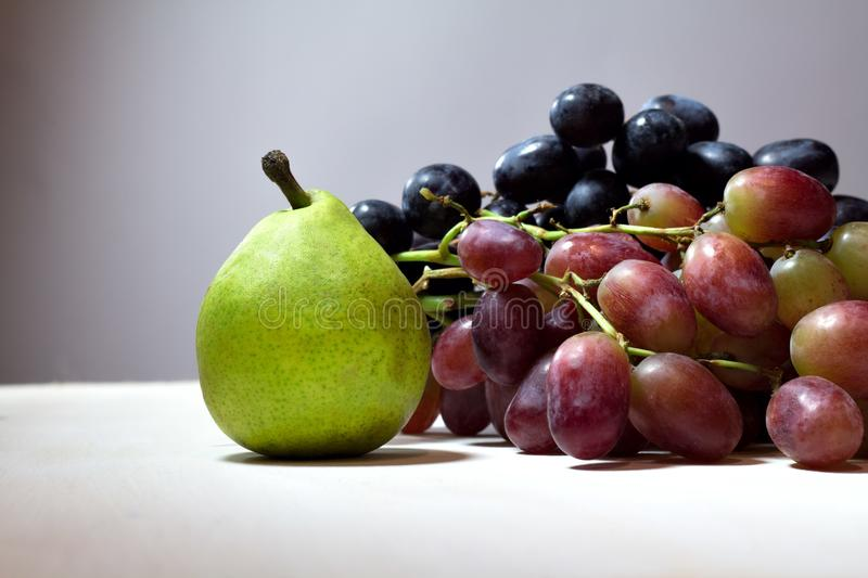 Still life with pear and grapes.. stock photos