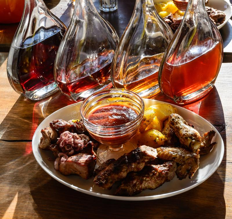 Still life. The photo shows a plate with juicy shish kebab and fried potatoes. In the background, decanters of transparent glass a royalty free stock images