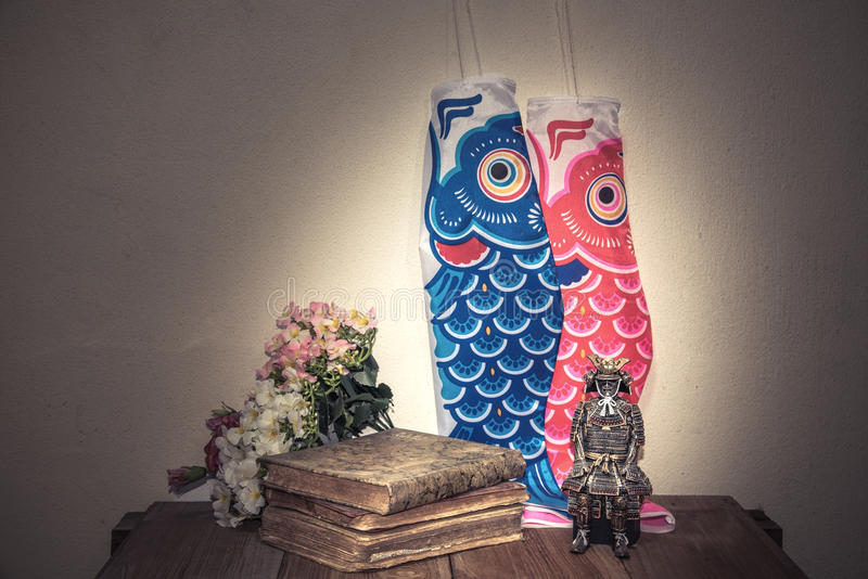 Still life photography. With Flower, Diary,Japanese Samurai statue and Carp kite on the wooden table and rough concrete wall back ground royalty free stock images