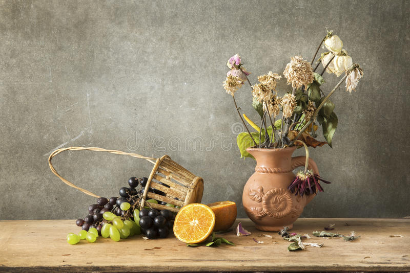 Still life Photography of friute and flower. Still life Photography with orange, grape and flower on wooden table and dark grunge background stock image