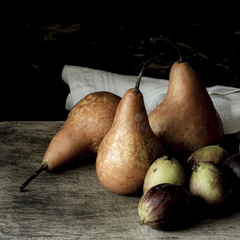 Still life photography of pears and figs on a wooden desk with a black background royalty free stock photos