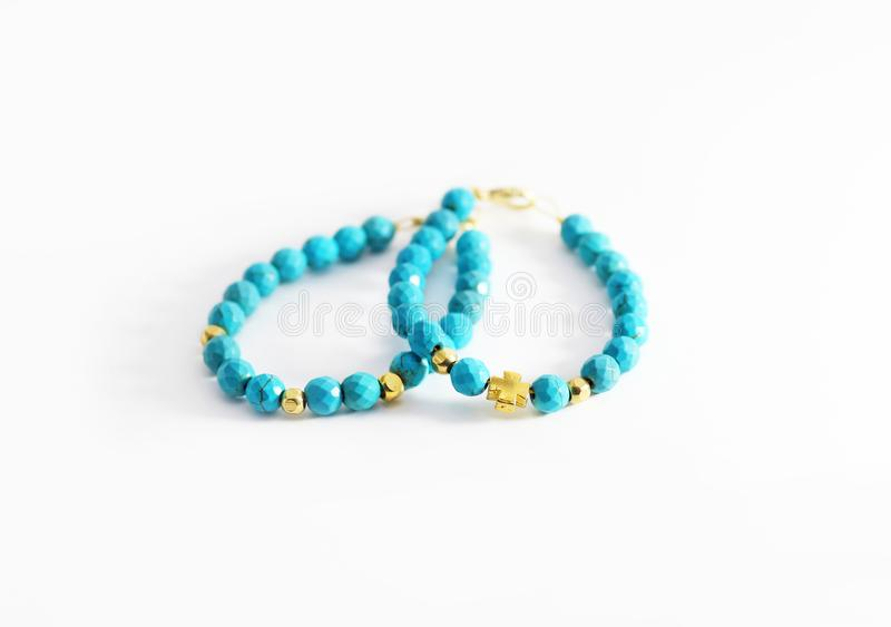 Still life photography of turquoise gemstone bracelets with golden beads and cross stock image