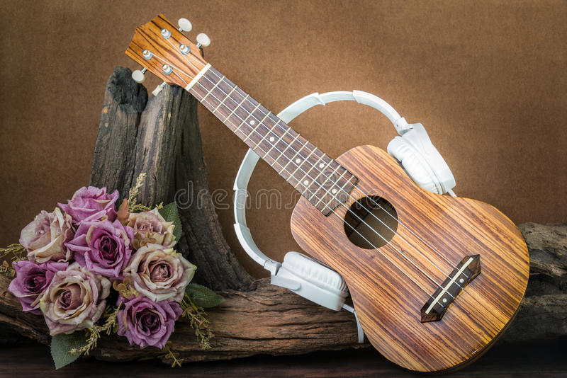 Still life photography with ukulele and headphone. On flower background vintage retro style, love music concept royalty free stock photo