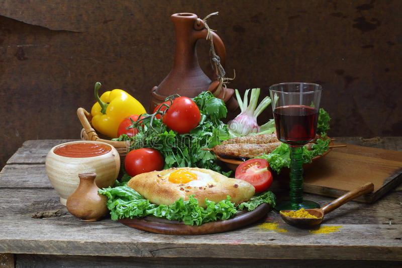 Still-life with a pie, fresh vegetables and red wine royalty free stock images
