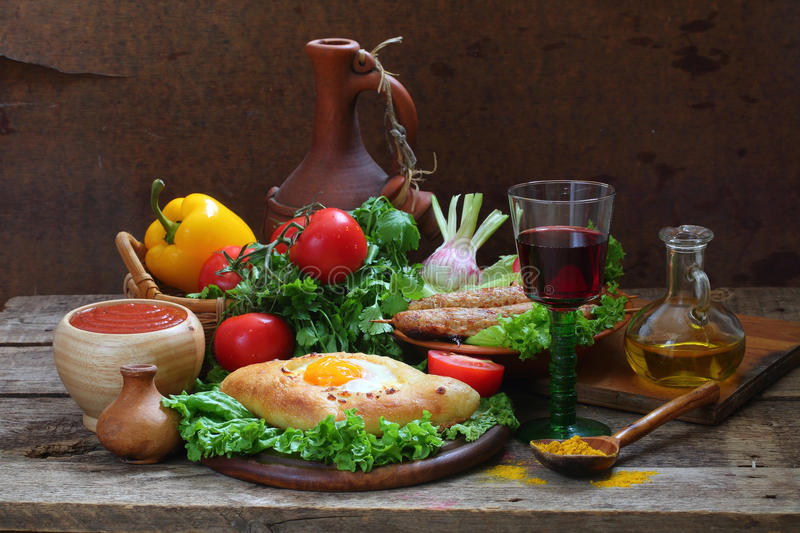 Still-life with a pie, fresh vegetables and red wine. On a wooden table royalty free stock images