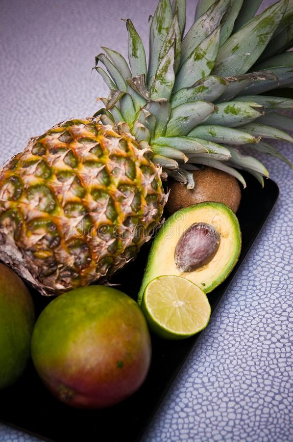 Fruit still life. Still life of a pineapple, avocado and lemon on a black tray, on an abstract alligator skin design background stock photo