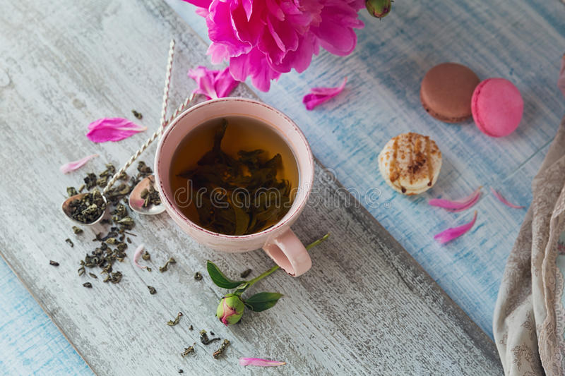 Still life with pink peony flowers and a cup of herbal or green stock images