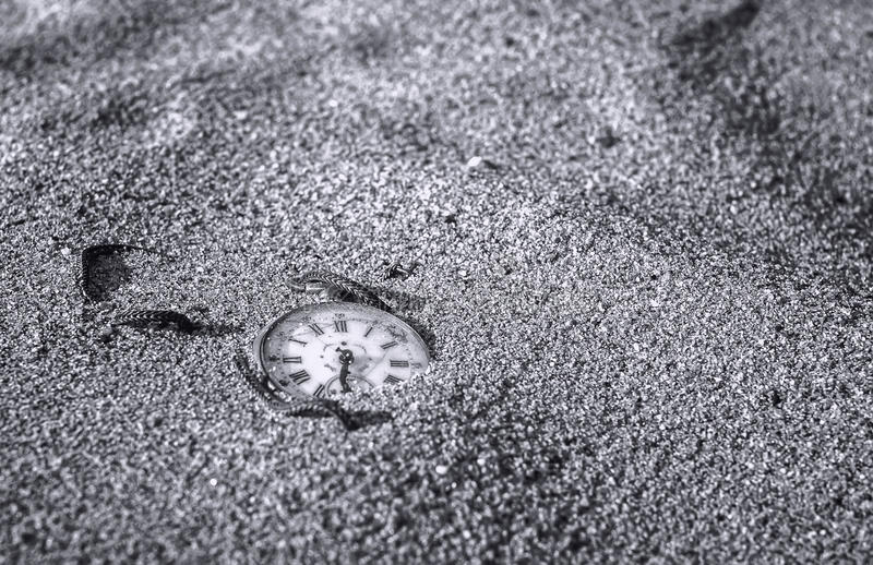 Still life - Pocket watch buried partial in the sand. Still life - Antique rotten pocket watch buried partial in the sand, black and white photography royalty free stock images