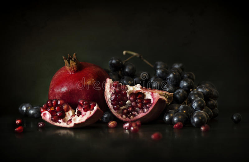 Still life of pomegranate and grapes stock photography