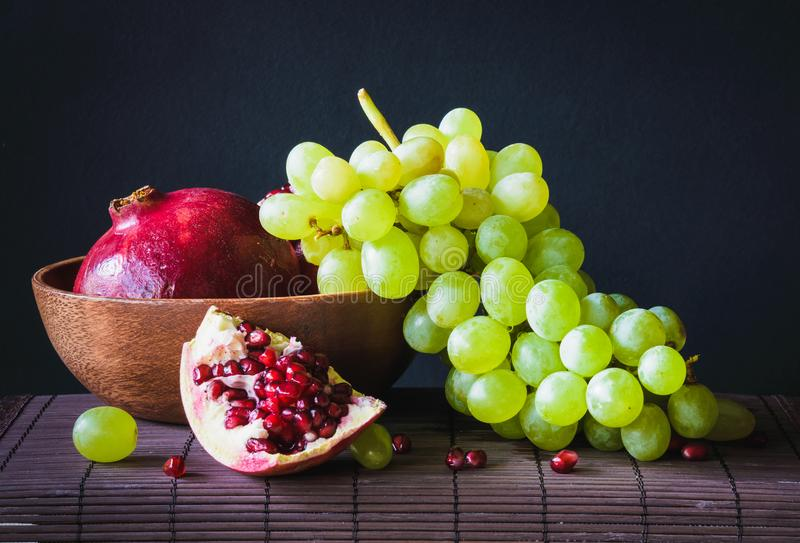 still life with pomegranate and green grapes on a dark background royalty free stock photography