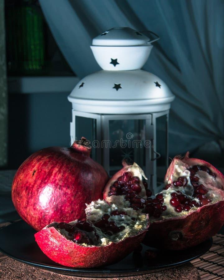 Still life with pomegranate and lantern. Still life with pomegranate. Juicy taste of the pomegranate. Freshness of summer. Fruits. Fruit freshness. pomegranate royalty free stock image