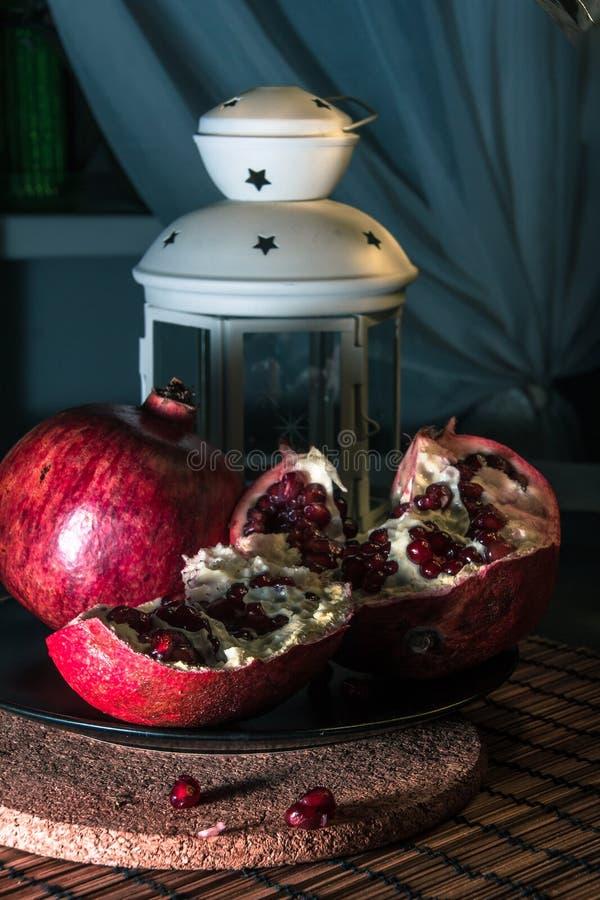 Still life with pomegranate and lantern. Still life with pomegranate. Juicy taste of the pomegranate. Freshness of summer. Fruits. Fruit freshness. pomegranate royalty free stock photo