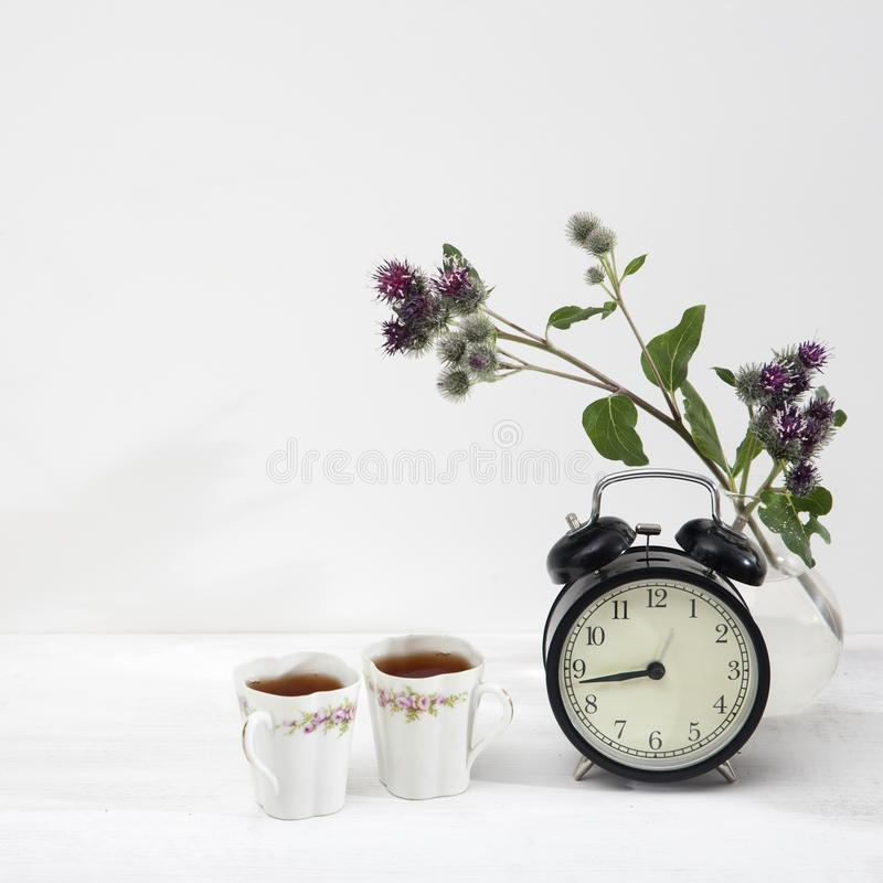 Still-life with porcelain cups with tea and burdock in a vase stock photos