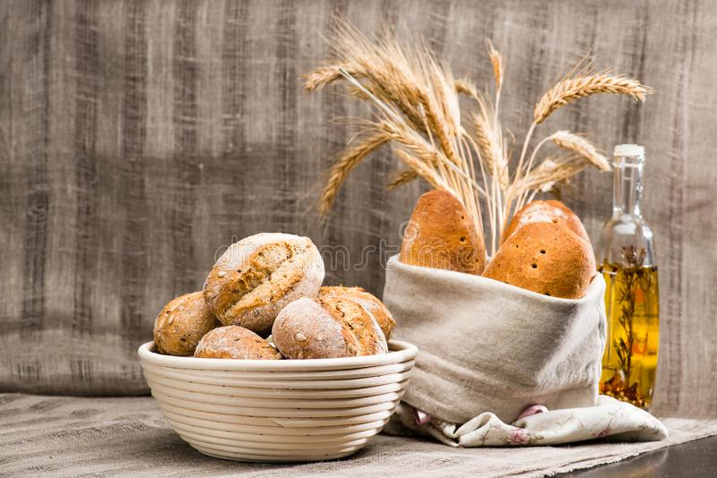 Still life with pugliese Apulian bread with biga covered with white fabric, a traditional round artisan wheat bread loaves in a b. Asket and olive oil bottle royalty free stock images