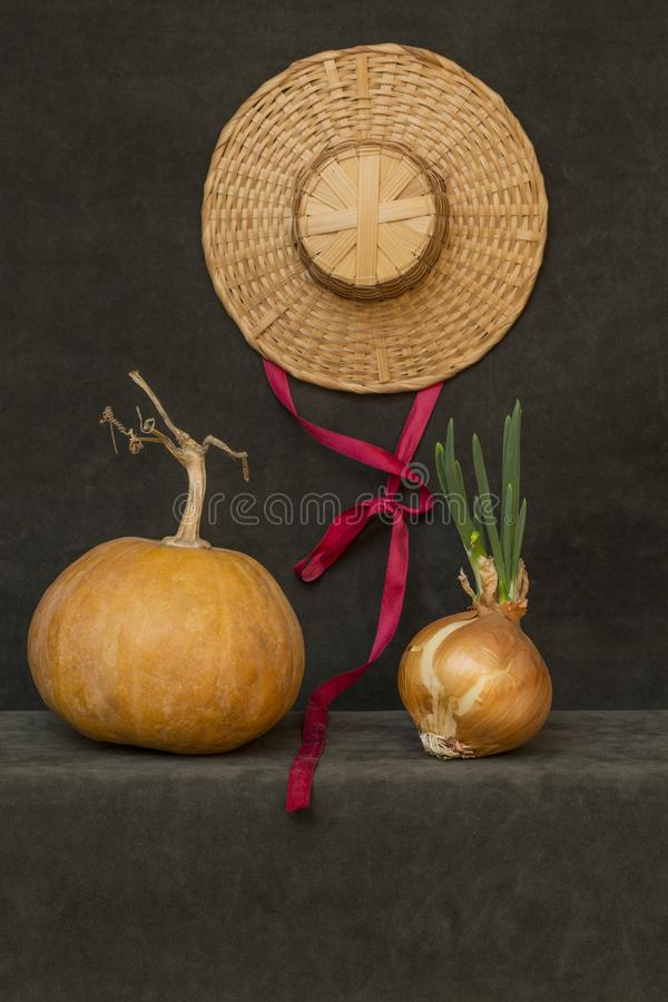 Still life with pumpkin, hat and sprouted onions. Still life with pumpkin, hat and sprouted onions stock images