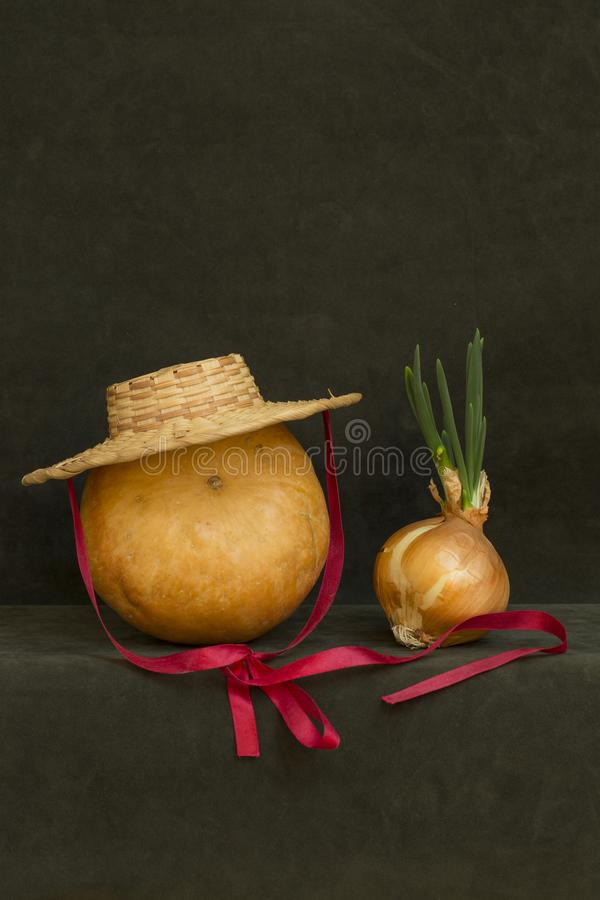 Still life with pumpkin, hat and sprouted onions. Still life with pumpkin, hat and sprouted onions royalty free stock photography