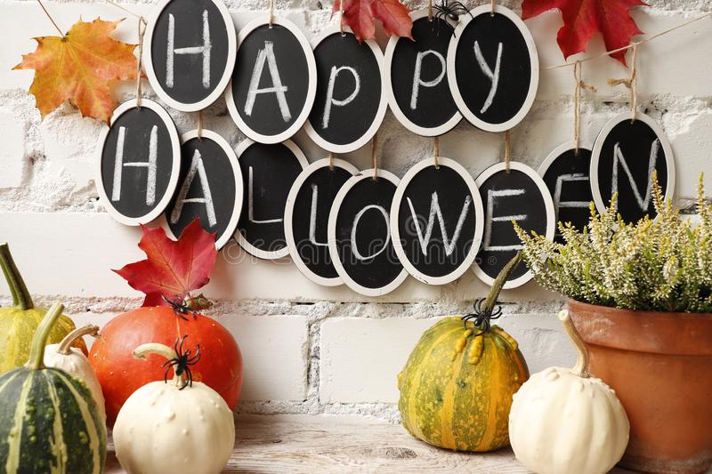 Text `Happy Halloween` and pumpkins. Still life with pumpkins and the text `Happy Halloween` against a white brick wall royalty free stock images